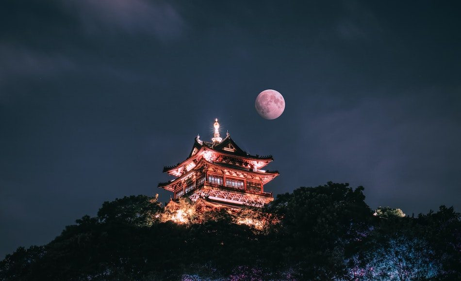 full moon above ancient chinese building at night