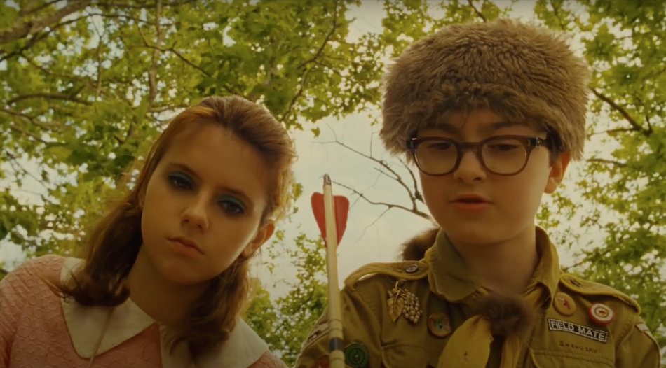 a young girl with blue eyeshadow and young boy with glasses and a scout uniform and 'davey crocket' hat hold an arrow in hand and stand above looking down