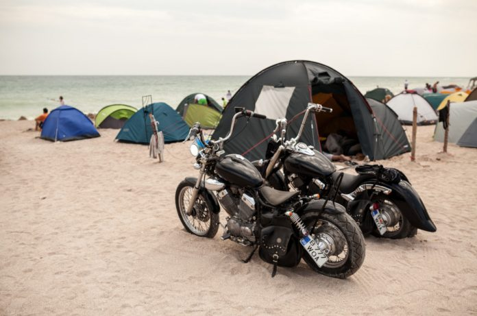 Two motorcycles on a beach with tents in the background.