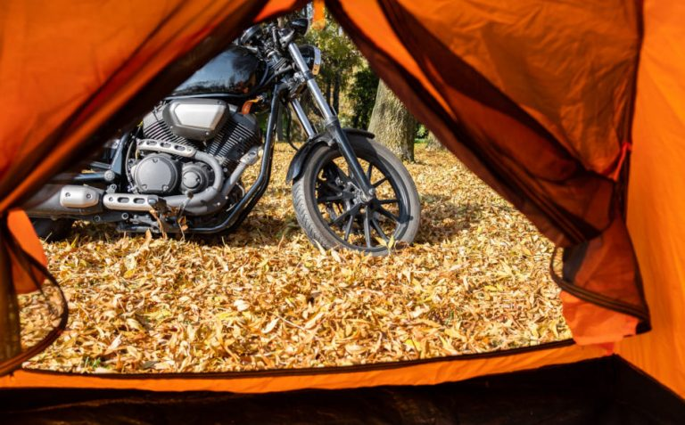 View from inside an orange tent looking out the flap at a black motorcycle parked on the leaf-strewn ground.