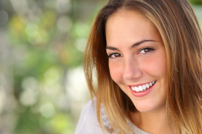 Brown-eyed woman with a beautiful white smile and blonde highlights in her hair with a green background.