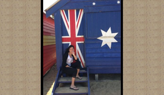 Laura Cozzolino sits in front of the colorful bathing boxes on Brighton Beach in Melbourne, Australia.
