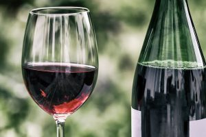 red wine in glass next to bottle