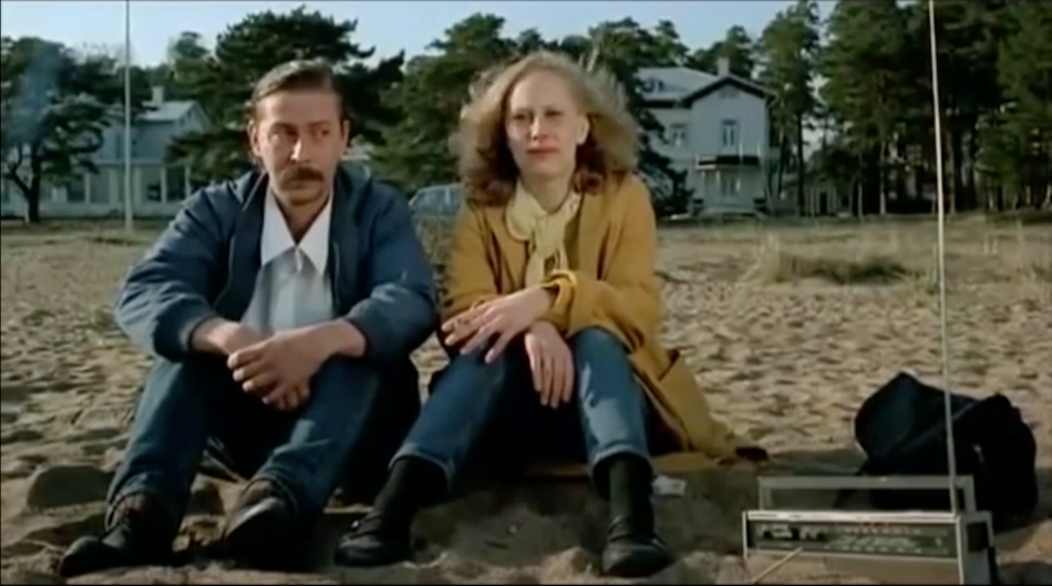 Couple sit on sand with a radio in Finland wearing jackets, jeans and boots.