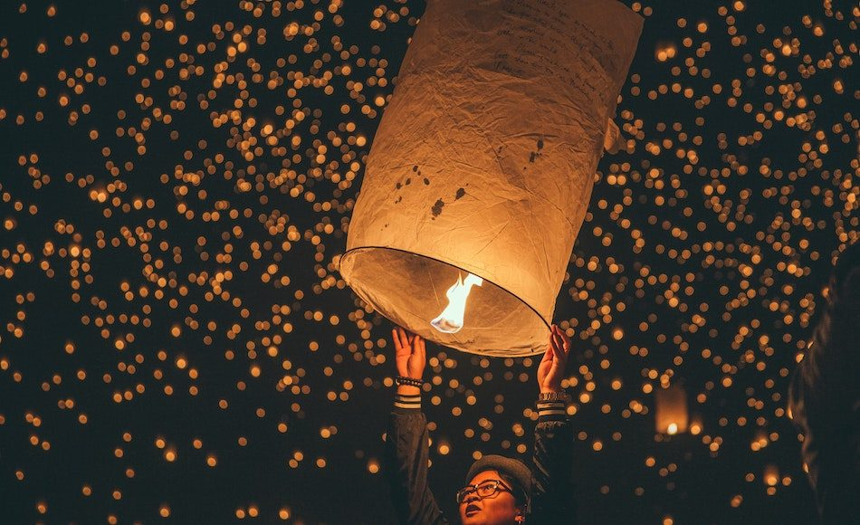 person releasing sky lantern into sky with many lit up behind her, we can see she has written what she wishes for in the New Year on the lantern.