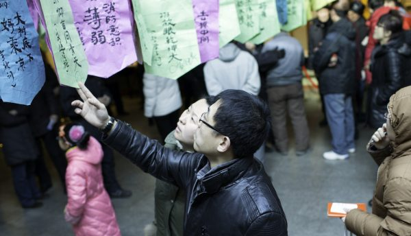 chinese couple look at riddles written on paper hanging up high, part of a tradition in the chinese lantern festival