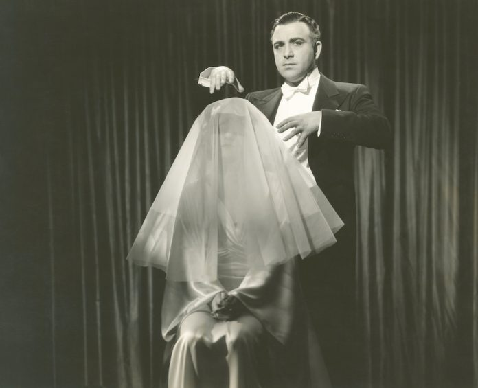 black and white photo of stage hypnotist with a woman who sits on a seat with a white sheer cloth on her head as she seems under the state of hypnotism