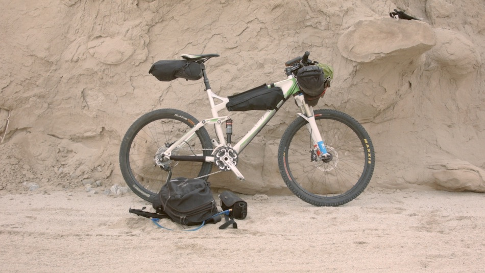 white mountain bike leaning up against rock formation