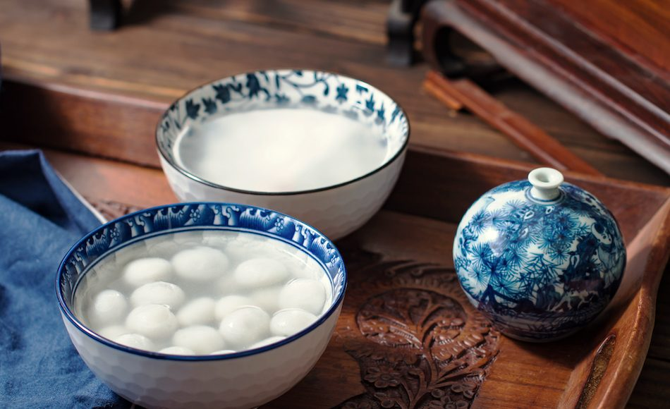 sticky rice balls in blue and white porcelain bowl with dark wood carved table and furniture in background.