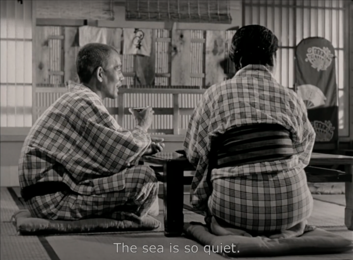 black and white film still of old japanese couple dressed in kimonos drinking tea with words 'the sea is so quiet' as a subtitle on screen. Send someone special a bouquet of flowers on Valentine's Day.