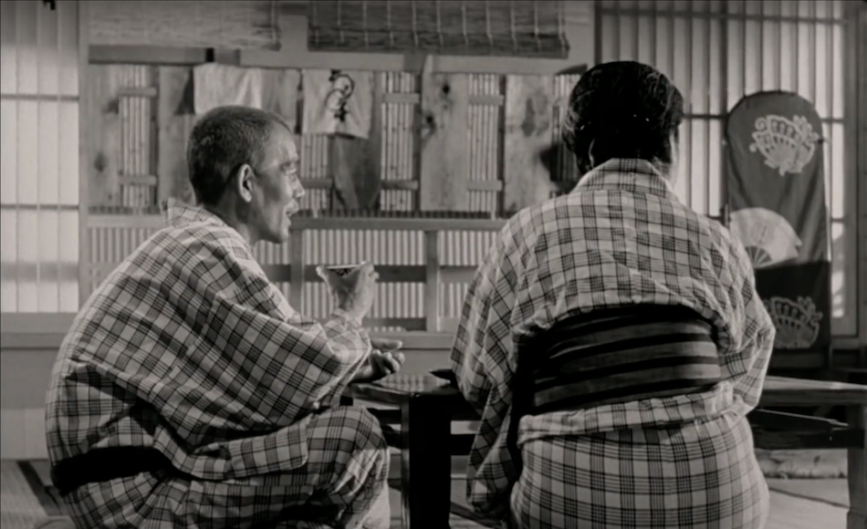 black and white film still of old japanese couple dressed in kimonos drinking tea with words 'the sea is so quiet' as a subtitle on screen.