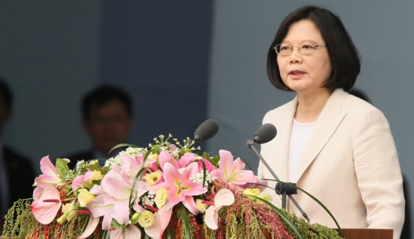Taiwan's President Tsai Ing-wen giving a speech at the inaugural ceremony activities in 2016 from a podium covered in flowers.