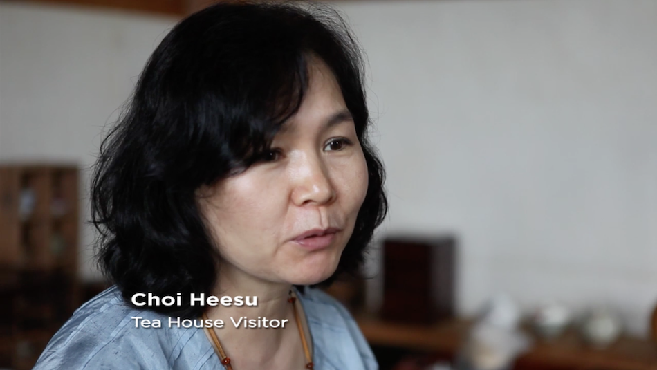 visitor to tea house, woman, black hair, gentle features, light blue top