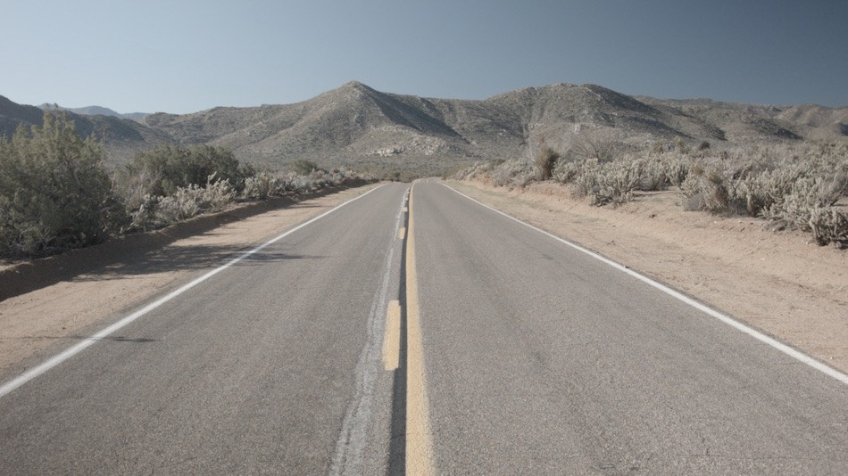 american road with no cars and mountains in background