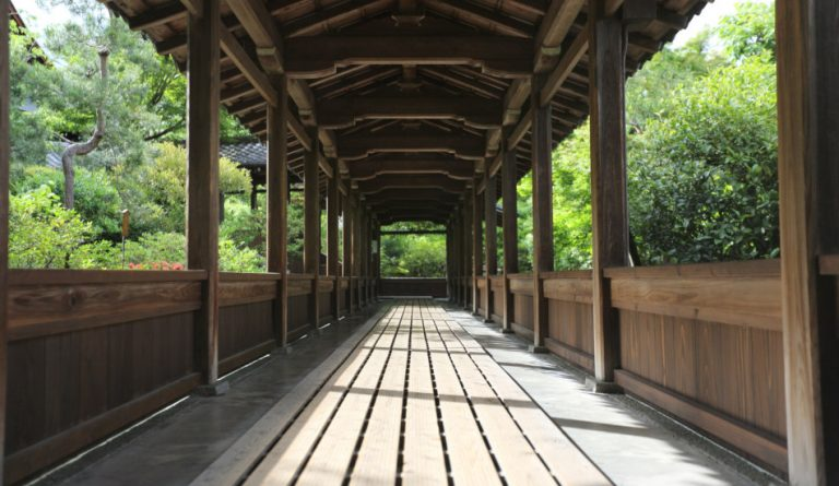 A wooden walkway in a Japanese temple garden in Kyoto.