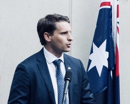 Australian politician, Andrew Hastie, giving a speech from a podium next to the Australian flag.