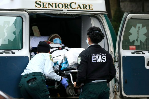Emergency Medical Service workers unload a patient out of their ambulance at the Cobble Hill Health Center on April 18, 2020 in the Cobble Hill neighborhood of the Brooklyn borough of New York City. New York Democrat Governor Andrew Cuomo is under fire for ordering discharged COVID-19 patients to nursing homes and covering up death statistics in his state