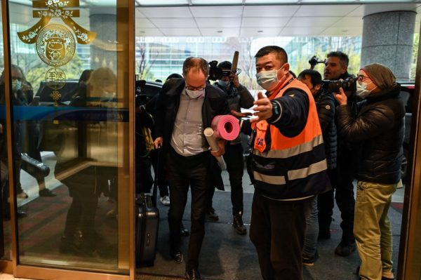 WHO team member Peter Ben Embarek (C) and other members of the group arrive at Tianhe International Airport to leave Wuhan in China's central Hubei province on February 10, 2021, after the team wrapped up an investigation into the coronavirus origin its team members described as clouded by politics
