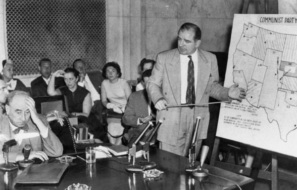 Black and white photo of Senator Joseph McCarthy standing to give a presentation in front of a map of the United States.