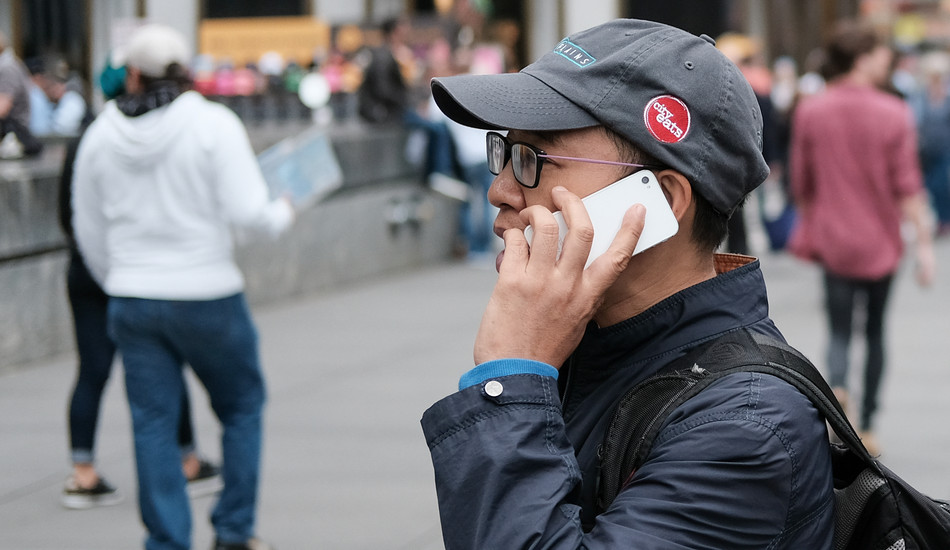 An Asian man talks on his cellphone just outside the Apple store in New York City.