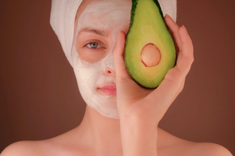 lady with hair wrapped in towel has a face mask on and is holding half an avocado over her eye
