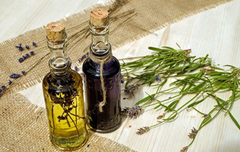 Two glass bottles with cork stoppers. One contains lavendar in oil and the other contains a purple liquid.
