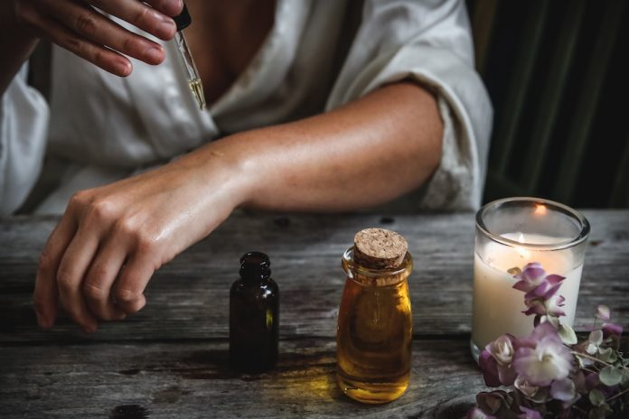 Natural Beauty Hacks - lady dripping oil on her skin as a beauty product with a dropper