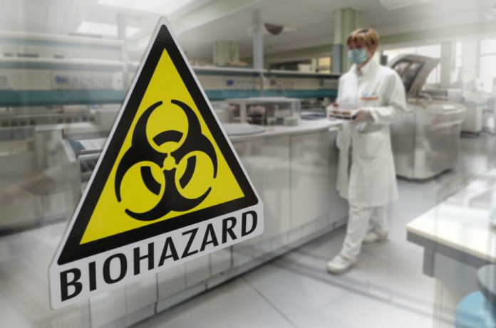 Biohazard sticker on the window of a laboratory with a technician carrying samples in the background.