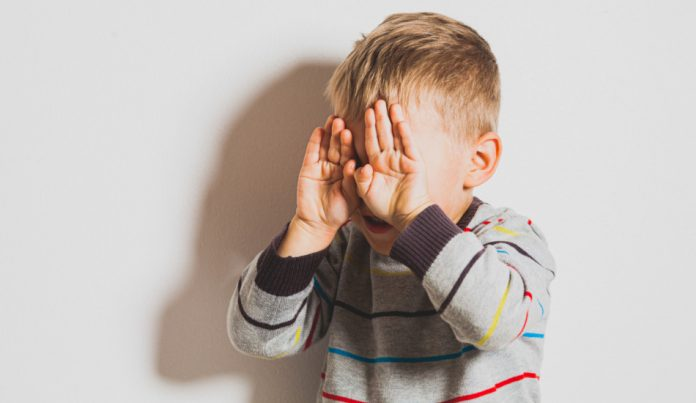 Frustrated little boy crying and covering his face.