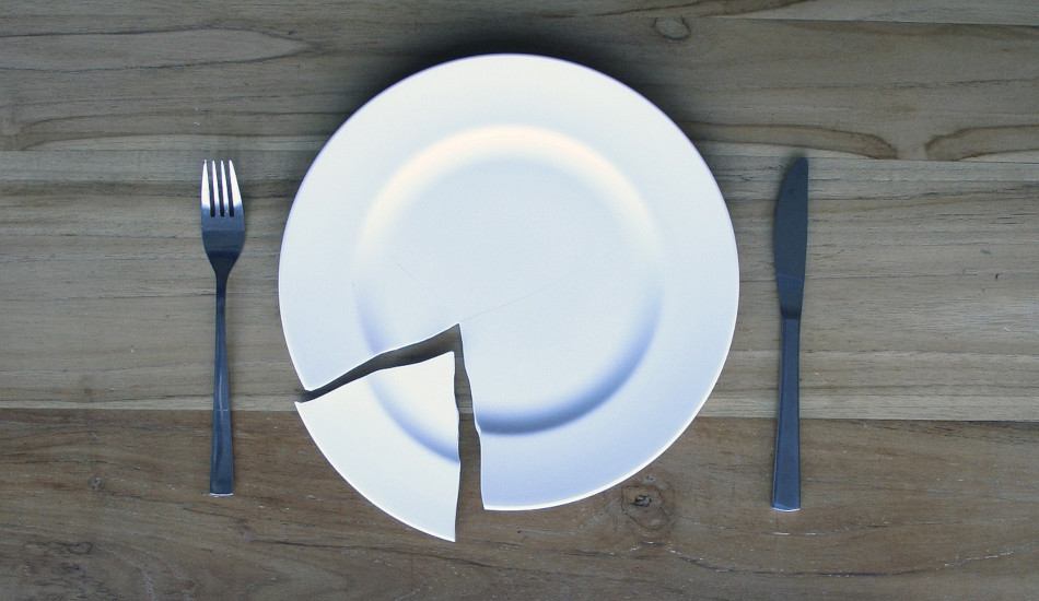 A broken plate sitting on a wooden table with a knife an fork.
