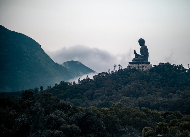 buddha statue on mountain surrounded by clouds