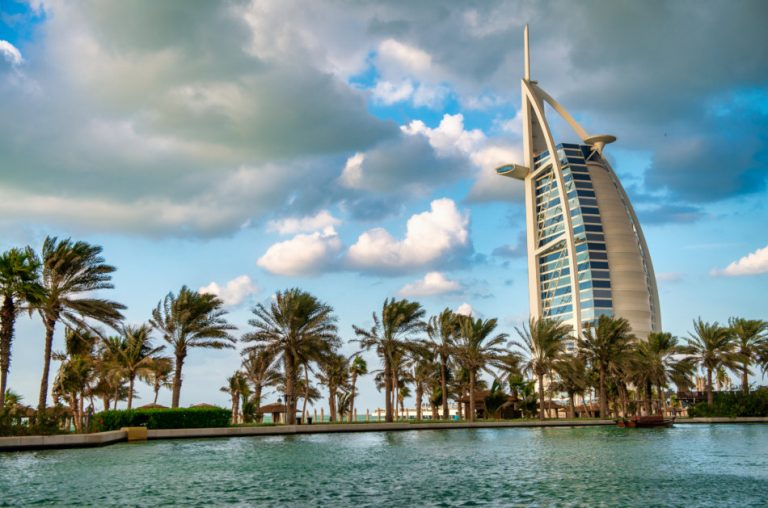 Dubai's Burj Al Arab hotel with palmtrees and water in the foreground.