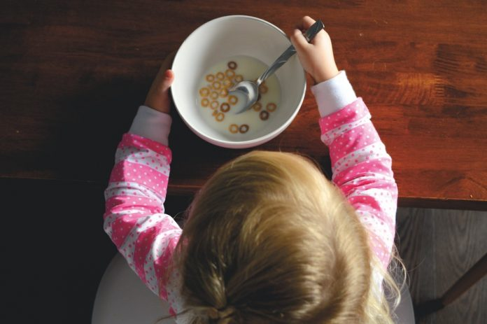 birds eye view of child eating cereal in a white bowl with milk