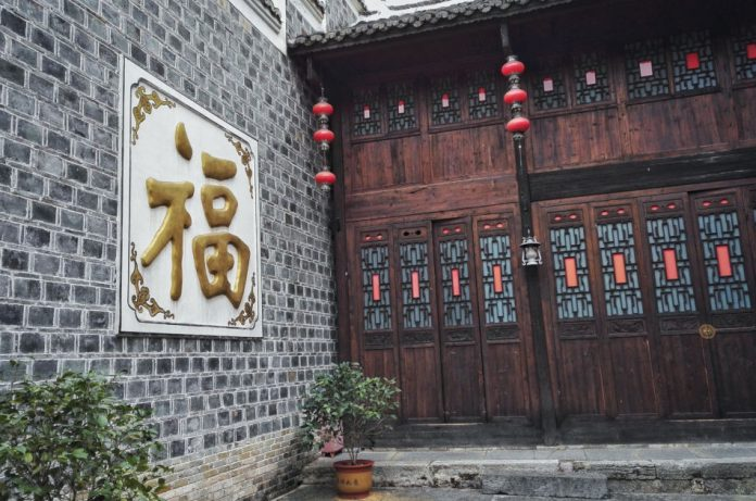 Chinese character 'fu' in gold on a plaque beside a wooden door. The character means 'good luck'.
