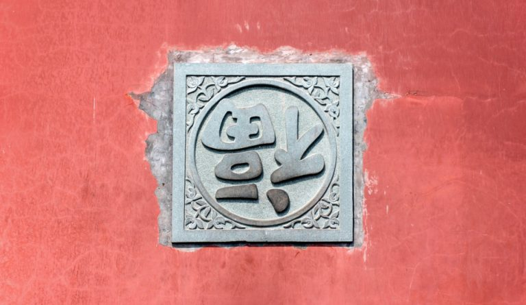 Upside down Chinese 'fu' character on red wall.