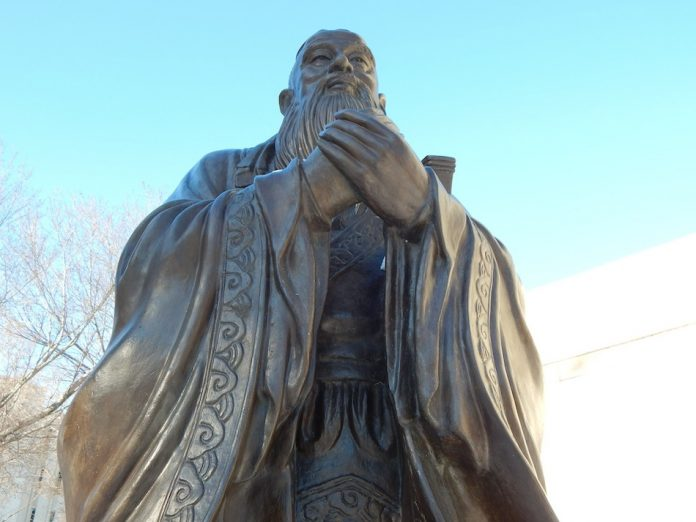confucius statue photographed from an angle down low looking up, confucius holds his hands together and wears an ancient robe