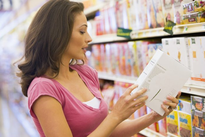 lady in grocery shop reading back of food label