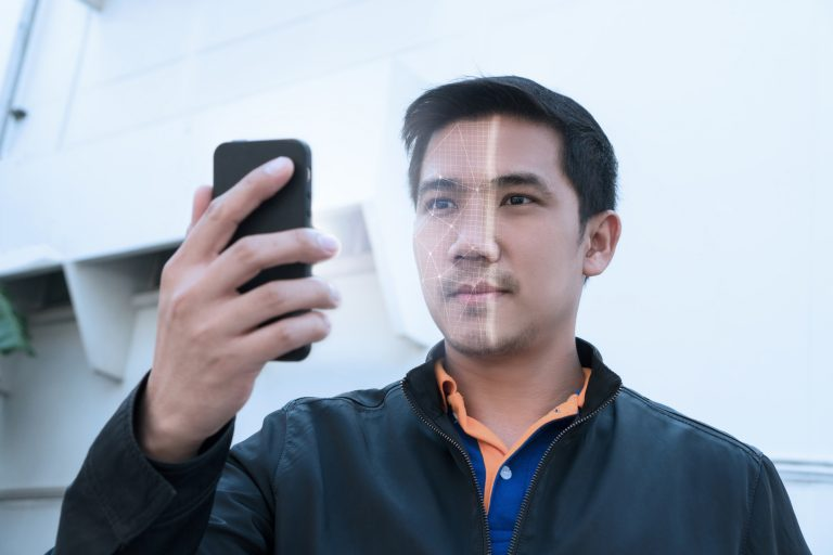 Asian man looking at phone with facial recognition.