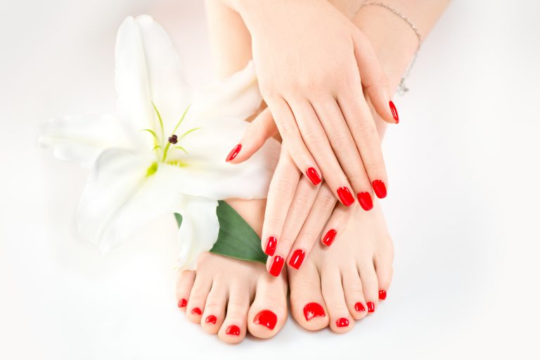 A woman'a hand and feet with red nail polish.
