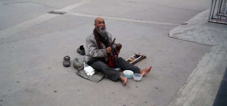 A man begging on the street.