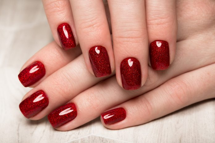 A women's long nails with red polish.