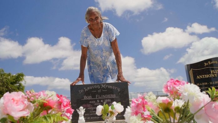 Aboriginal lady stands behind a grave filled with bright fresh flowers there s a blue sky with white clouds behind her, the scene looks almost heavenly.