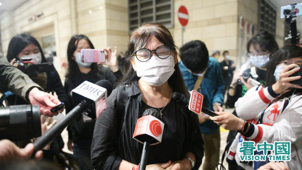 The mother of a pro-democracy activist wearing black clothing cries as she talks to reporters in Hong Kong outside the West Kowloon Law Courts Building.