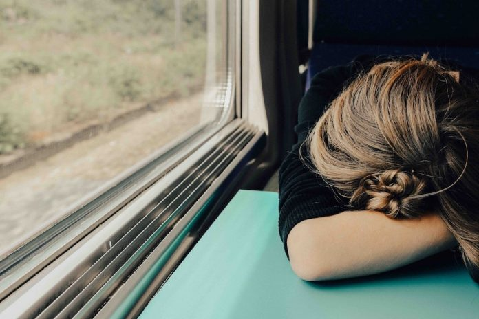 lady resting head on table while travelling on train
