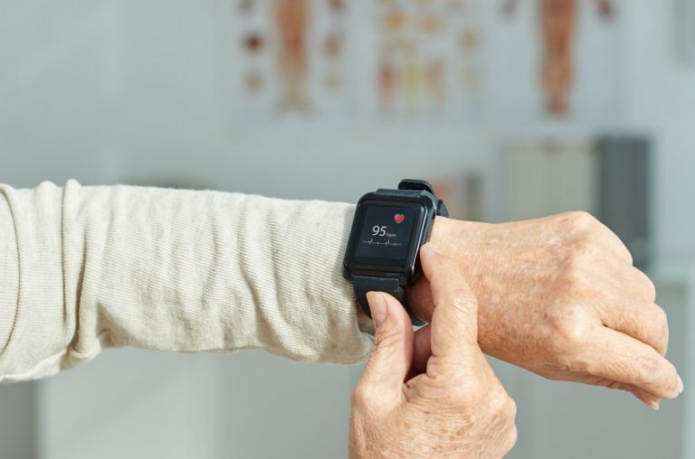 Close up of a fitness tracker showing a woman's heart rate.