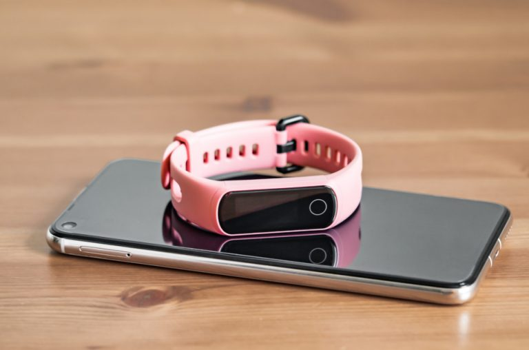 A pink fitness tracker sitting atop a smartphone on a wooden table.