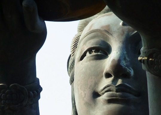 detail of statue bodhisattva Guan Yins face from large statue in Hong Kong