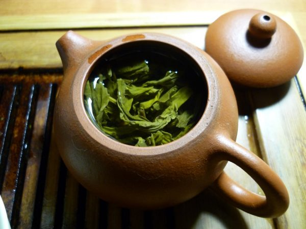 Green tea brewing in a clay pot ready to nourish and hydrate the skin