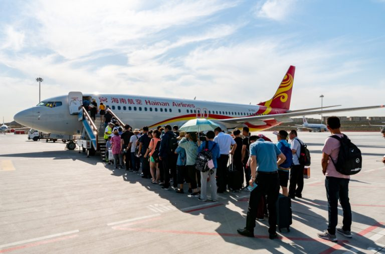 Passengers are standing in line on the tarmac waiting to board a Hainan Airlines plane.