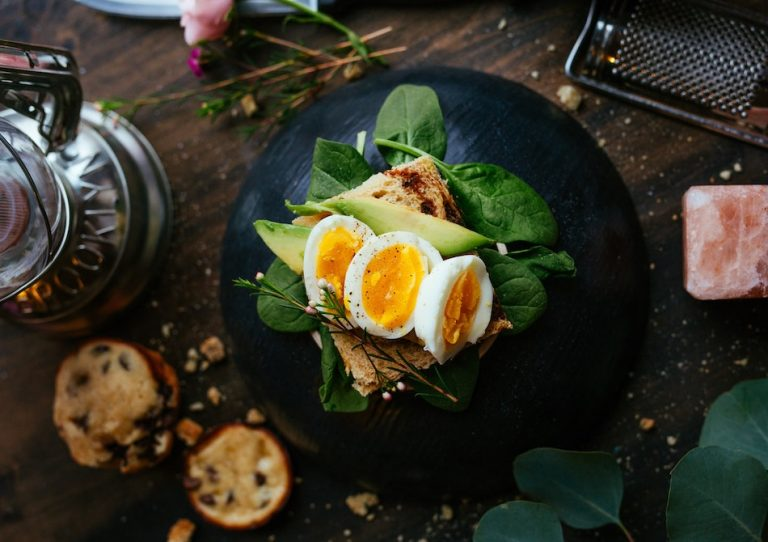 boiled eggs on spinach with avocado and sourdough bread